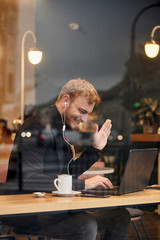 one young smiling man, sitting in coffee shop and using his laptop, gesturing with his hand Hello or Hi, waving his hand over video conference call. Shoot thought window outside (with reflections).