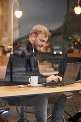 one young happy man, sitting in coffee shop and using his laptop, typing on keyboard, looking to computer screen. Shoot thought window outside (with reflections).