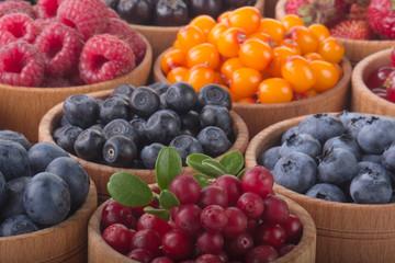 berries in wooden cups background