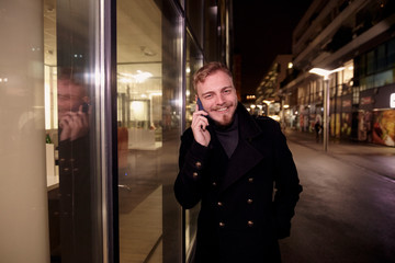 night time, one young smiling and happy man, 20-29 years, talking over his phone, standing in Autumn coat on street, in front of business offices windows outdoors, looking to camera.