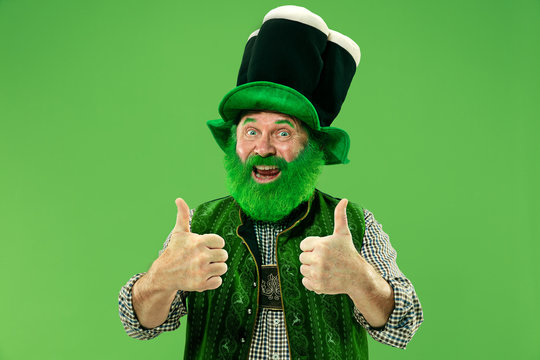 A smiling surprised happy senior man in a leprechaun hat with beard at green studio. He celebrates St. Patrick's Day. The celebration, festive, beer, holiday, alcohol, party, human emotions concept