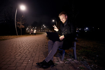 dark night, one young man, 20-29 years, sitting on bench alone, using his laptop in public park in Autumn. gesturing Hello or Hi, with two fingers as a greeting, over video conference call or chat.