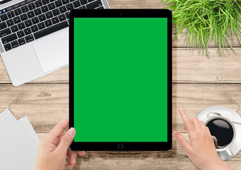 Human hand holding tablet with green screen for video production