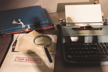 Investigator desk with confidential top secret documents, magnifying glass and typewriter. Shadow from the hand of a thief or secret agent. Vintage tone.