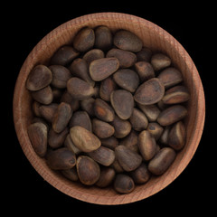cedar nuts in wooden cup isolated on black background. top view