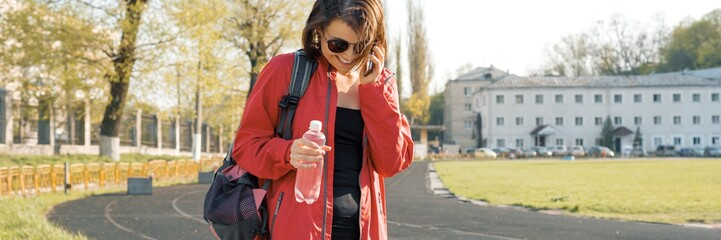 Portrait sporty mature woman at the stadium, panoramic banner, in sports clothes for training, with bottle of water, talking on the phone