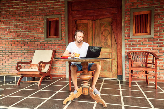 Man with smartphone, coffee / tea and laptop on a home porch.