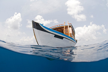 Diving boat of the Maldives from beneath the water line in tropical sea