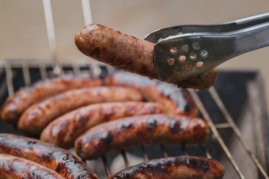 Grilling sausages on barbecue grill outdoor