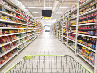 shopping cart with abstract blurred supermarket aisle with colorful goods on shelves at background, sign of product for cooking hanging from ceiling
