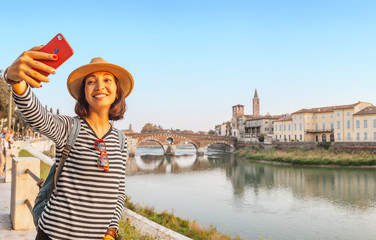 Smiling traveler woman taking selfie on her smartphone at the background of the Verona Bridge Ponte Pietra, in Italy