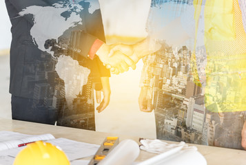 Closed up of businessman shake hands with engineering in construction renovate building site.(Outline elements of world map image from NASA public domain)