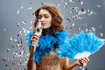 Woman in a blue boa is standing in the studio holding a fan of feathers in her hand and drinking champagne