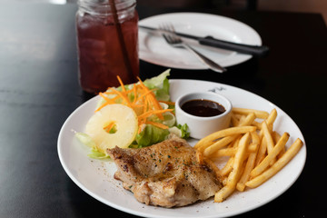 chicken steak with French fries and sauce on table