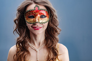 Closeup portrait of smiling brunette girl in carnival mask and pearl necklace