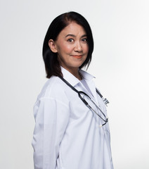Asian Beautiful Senior Doctor Nurse woman in uniform with stethoscope in Medical hospital, portrait 50s 60s years old aging society make up black short hair, studio lighting gray background copy space