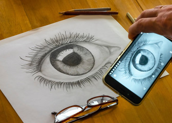 The hand of the artist is making the photo from of the woman's eye made by himself in grayscale. The picture is on the white paper. The picture of this composition made by middleformat camera.