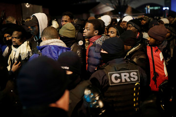 Migrants stand in line as French police evacuate hundreds of migrants living in makeshift camp set up in Saint-Denis outside Paris