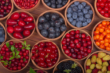 berries in wooden cups on wooden background. top view