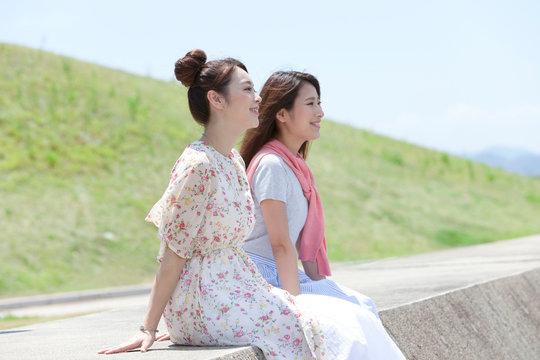 堤防に座る女性2人