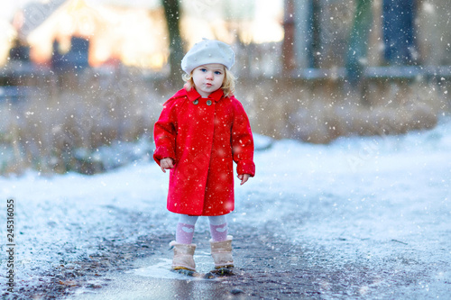 37843417e Outdoor winter portrait of little cute toddler girl in red coat and white  fashion hat barret. Healthy happy baby child walking in the park on cold  day with ...