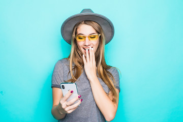 Portrait of outraged confused woman wearing fluppy hat and sunglasses holding and looking at mobile phone isolated over blue pastel background