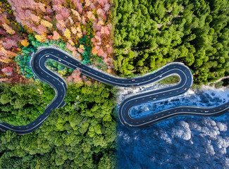 Winding road in all four seasons. Aerial view of a curved highway trough the forest. Composite drone roadway image