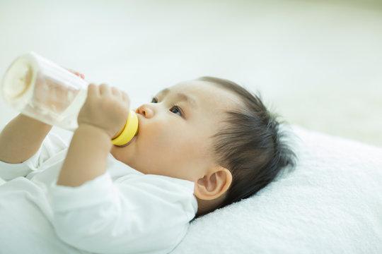 哺乳瓶に入ったミルクを飲む赤ちゃん
