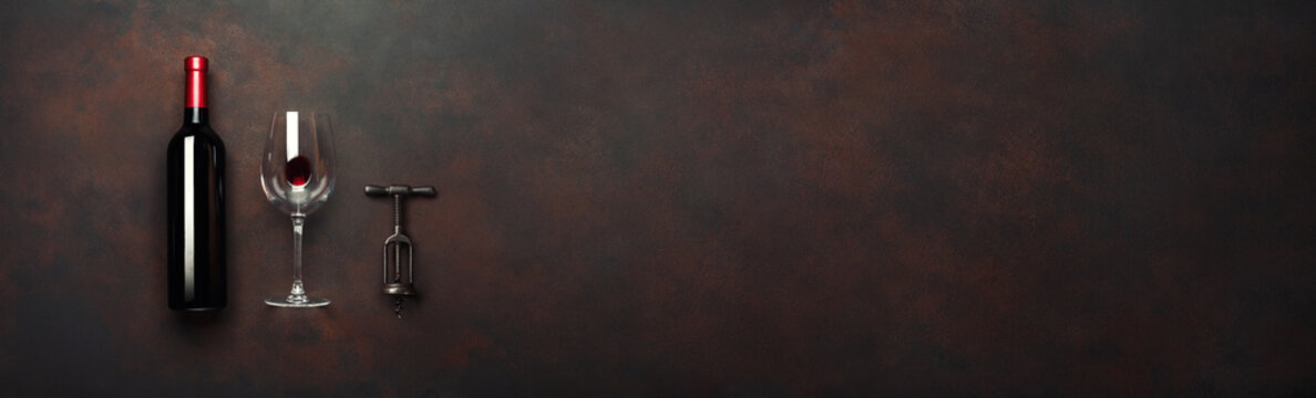 Bottle of wine with wineglass and corkscrew on rusty brown background. Panoramic top view with space for your text