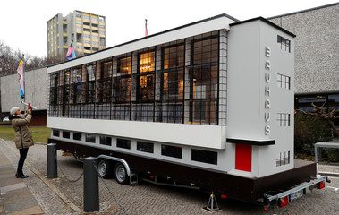 "A woman takes a picture of a tiny house called ""Wohnmaschine"" in a version of the Bauhaus school building in Dessau to mark 100th anniversary of Bauhaus in Berlin"