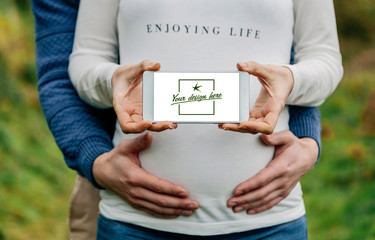 Pregnant woman showing customizable screen of the mobile embraced by her partner