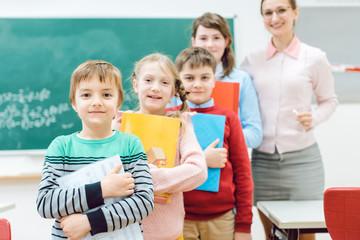 Schüler mit Büchern und die Lehrerin stehen im Klassenzimmer