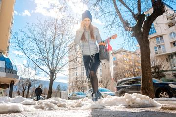 Frau läuft durch Matsch, Schnee und Tauwasser