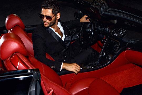 Men in luxury car. Night life.