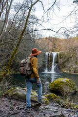 Unrecognizable traveler standing near pool and waterfall