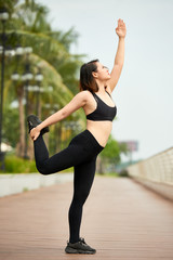 Side view of young ethnic woman in sportswear training yoga on seafront holding arm raised