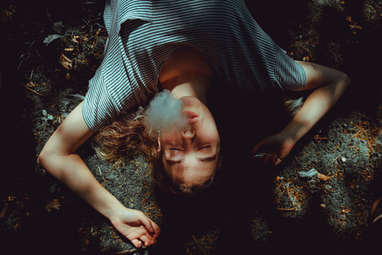 Woman with smoke from mouth lying on ground
