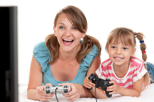 Mom and Daughter holding Joysticks and Playing Video Games on console together. Happy Family - Mother and little Girl having Fun gaming on white background. Woman with Child playing Computer Game.