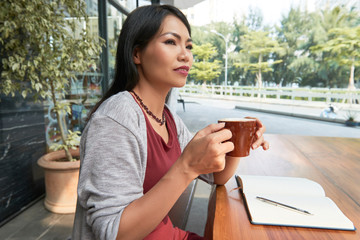 Asian serious woman sitting at the table with open notebook and enjoying the cup of coffee at outdoor cafe