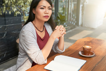 Asian serious woman sitting at the table with notebook and thinking about new ideas at cup of coffee at cafe