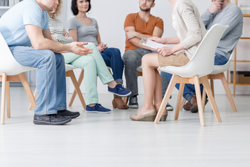 Close-up on psychotherapist talking with group of people with problems during therapy