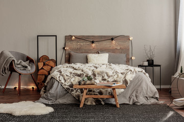 Trendy grey chair with blanket and log of wood next to cozy double bed with wooden headboard and light bulbs