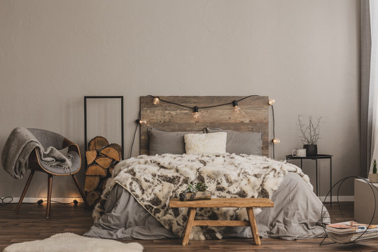 Stylish grey chair with blanket and log of wood next to warm double bed with wooden headboard and light bulbs