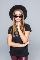 Fashion portrait pretty sweet young woman wearing a black hat sunglasses coat over grey background