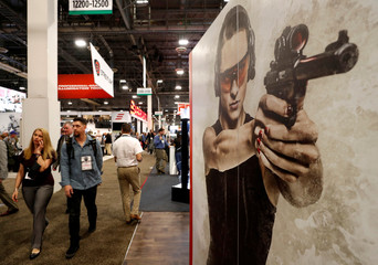 Attendees walk by a photo of a female shooter at the Aguila Ammunition booth during the SHOT Show in Las Vegas
