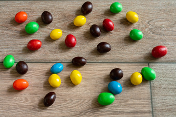 Coated chocolate is arrayed on wooden floor. Fotoväggar
