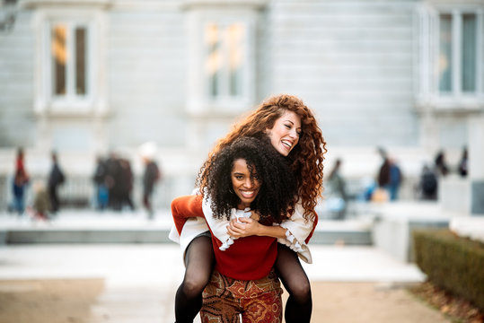 Two cheerful young women playing piggy back