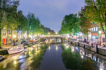 Canal with boats and bicycles on the street at night in Amsterdam, Holland