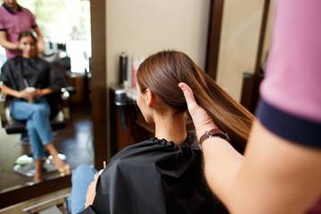 A male hairdresser combs her long dark hair client