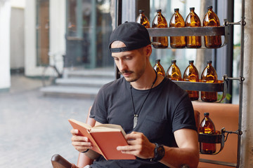 Portrait of young Caucasian man has morning drink in coffeeshop, sits on wooden designed chair, reads book, prepares for examination, has pensive concentrated look, dressed in casual sporty clothes.